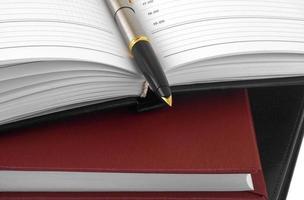 öppen anteckningsbok och penna för att skriva foto