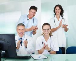 lyckligt medicinskt team som ger tummen upp foto