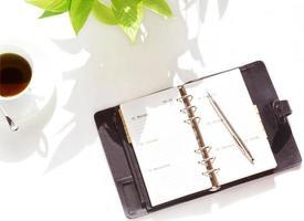 anteckningsbok och kaffekopp foto