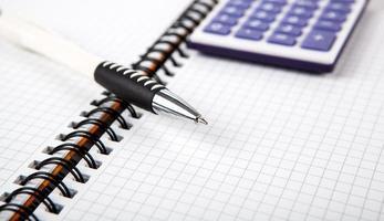 penna på en anteckningsbok i en cell och miniräknare foto