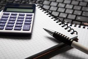 penna med miniräknare på en anteckningsbok och tangentbord foto