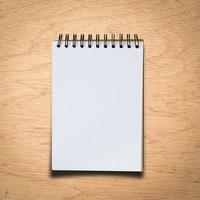 svart anteckningsbok på en träbakgrund med urklippsbana foto