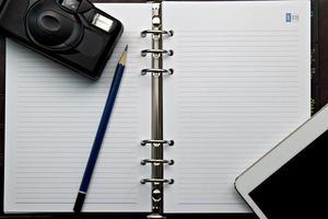dagbok och retro kamera med digital tablet pc foto