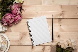 anteckningsblock med penna på träbakgrunden foto