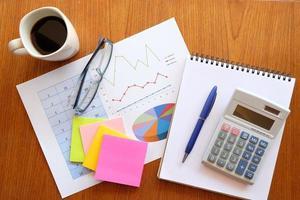 anteckningsbok och diagram på träbord med kaffe foto