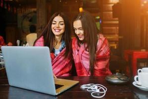 två flickor tittar på något i bärbar dator foto