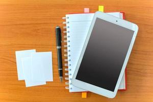 surfplatta och anteckningsbok på träbord foto