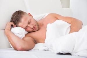 man sover i sängen foto