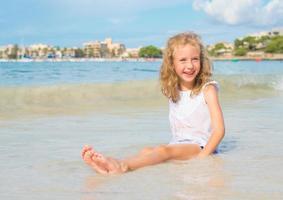 liten flicka som har kul på strandsemester. plats för text. foto