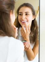 tonåring applicerar läppstift foto