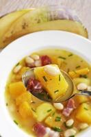 svensksoppa med vita bönor och bacon, sked och tallrik foto