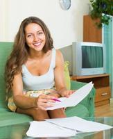 kvinna fylla papper hemma foto