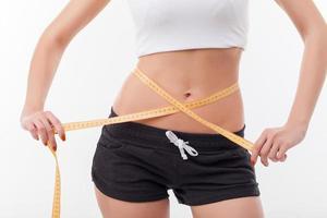 ung smal tjej mäter sin kropp foto