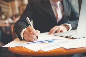 unga affärsmän som använder anteckningsboken och en penna foto
