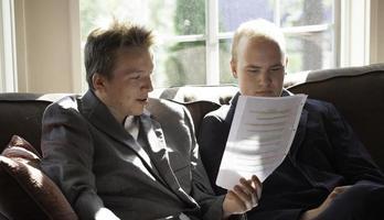 två unga vuxna talar om ett papper foto