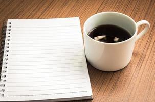tom anteckningsbok och kaffe på träbord foto