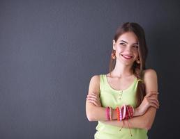 ung kvinna stående, isolerad på grå bakgrund foto