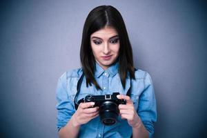 förvånad ung kvinna som tittar på kameraskärmen foto