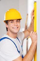 reparatör mätning med byggmästarnivå foto