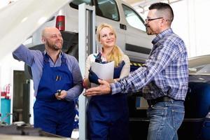 servicepersonal och förare nära bilen foto