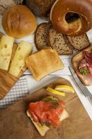 frukost med graven lax på rostat bröd, skinka, ost, bagel foto