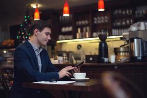 ung attraktiv affärsman i kostym som dricker kaffe och använder foto
