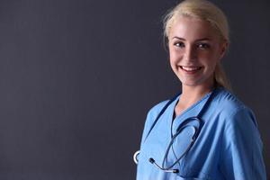 ung läkarkvinna med stetoskop isolerat på grått foto