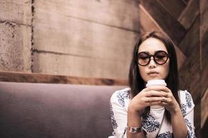 asiatisk kvinna som dricker kaffe med tanke på ett kafé foto