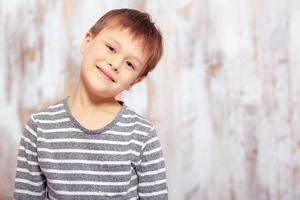 porträtt av en söt emotionell liten pojke i sängen foto