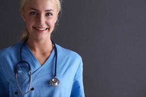 ung läkarkvinna med stetoskop isolerad på grå bakgrund foto