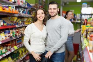 kunder som står nära hyllor med konserver på butiken foto