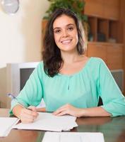brunett kvinna fylla papper hemma foto
