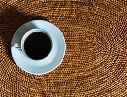 kaffekopp på en flätad placemat foto
