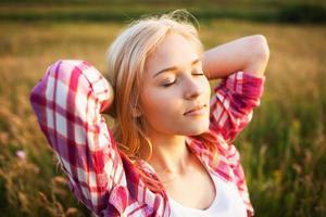 glad blond kvinna med slutna ögon foto