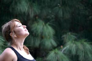 kvinna andas in doften av naturen foto