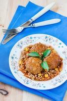 köttbullar i tomatsås med grönsaker foto