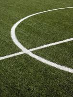 del av fotbollsplanen med grönt syntetiskt gräs närbild foto