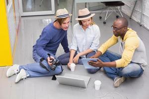 tillfälliga kollegor som använder digital surfplatta på golvet foto