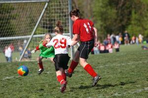 tjej sparkar bollen i mål foto
