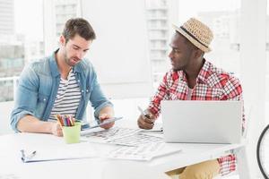kollegor som sitter med surfplatta och bärbar dator foto