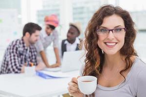 leende affärskvinna håller kopp kaffe foto