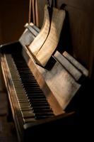 antikt piano med gamla musikark i solljus foto