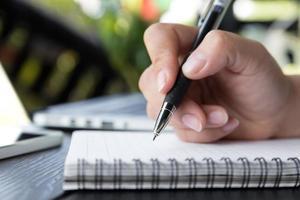 hand håller en penna skriva på anteckningsboken foto