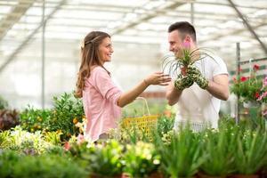 säljaren rekommenderar blommor i växthus foto