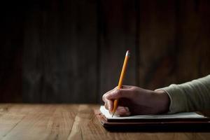 kvinnans hand skriva på papper foto