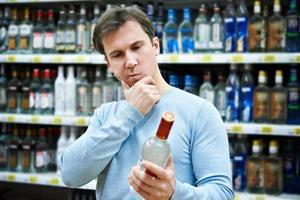 man väljer en flaska vodka foto