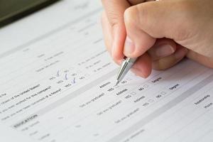 hand med pennan över tomma kryssrutor i ansökningsformuläret foto