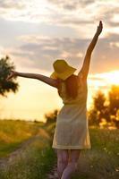 flicka i en klänning och hatt går vid solnedgången