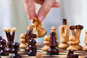 schackspelarens hand med riddaren foto
