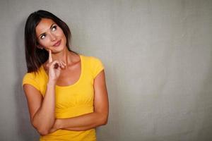 fundersam brunett dam tänker medan du tittar bort foto